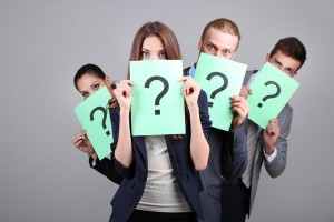 Business team standing in row with question mark on grey backgro
